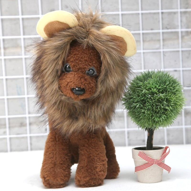 A stuffed animal dog with lion wig, next to a plant in a pot.