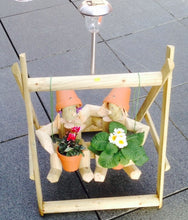 Couple on a swing with a solar lamp
