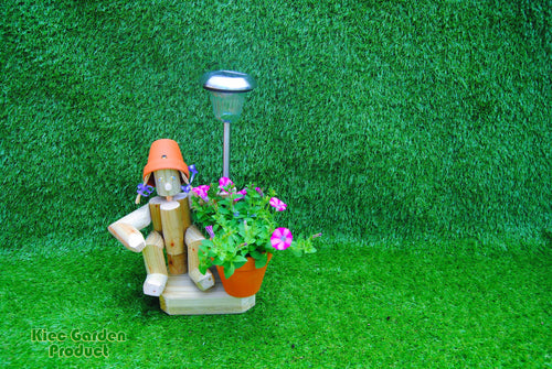 Small sitting girl holding a pot with solar light