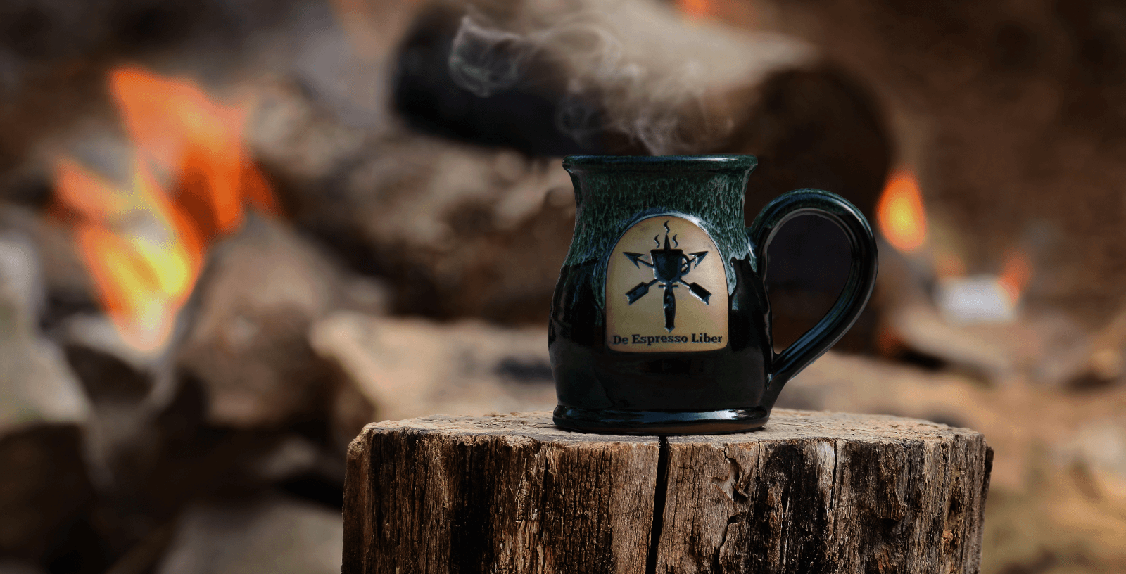 A steaming De Espresso Liber Green Tall Belly mug set in front of a warm campfire.