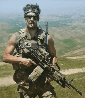 Image of Charles 'Chuck' Keating with light machine gun and Afghanistan in the background.