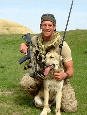 Image of Charles 'Chuck' Keating kneeling in Navy SEAL equipment next to dog in Afghanistan