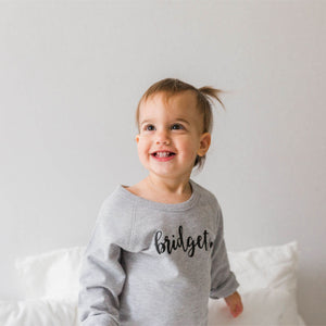 Little girl smiling into the distance.  Her grey sweatshirt has her name written on it.