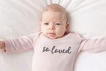 "A baby girl is lying on a bed, wearing a pink bodysuit that says ""so loved""."