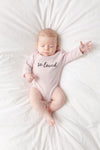 "A baby girl is lying on a comforter.  She is wearing a pink bodysuit that says ""so loved."""