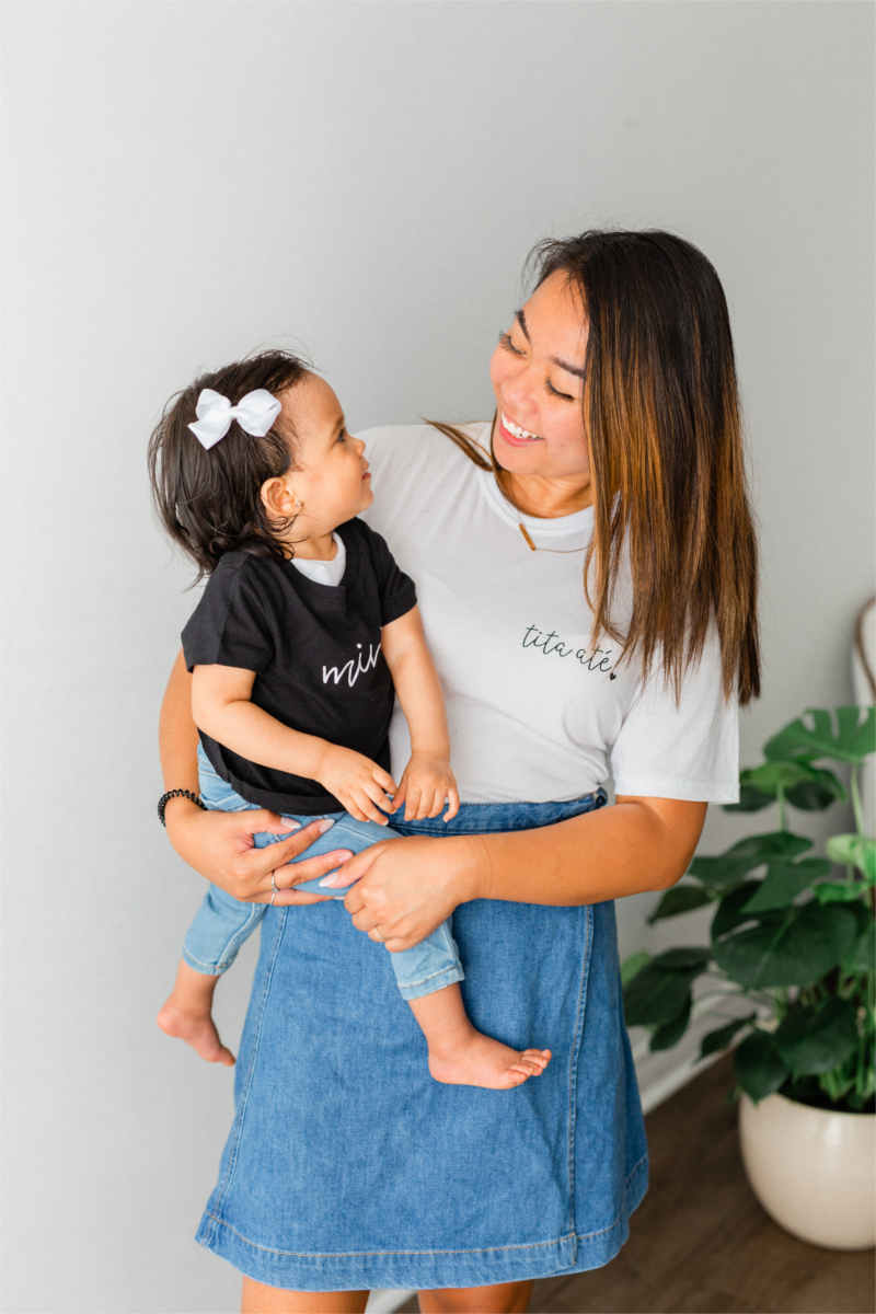 "A woman is holding a little girl.  They both have dark hair and the little girl is wearing a bow. The little girl is wearing jeans and a black t-shirt that says ""mini"".  The woman is wearing a jean skirt and a white t-shirt that says ""tita ate."""