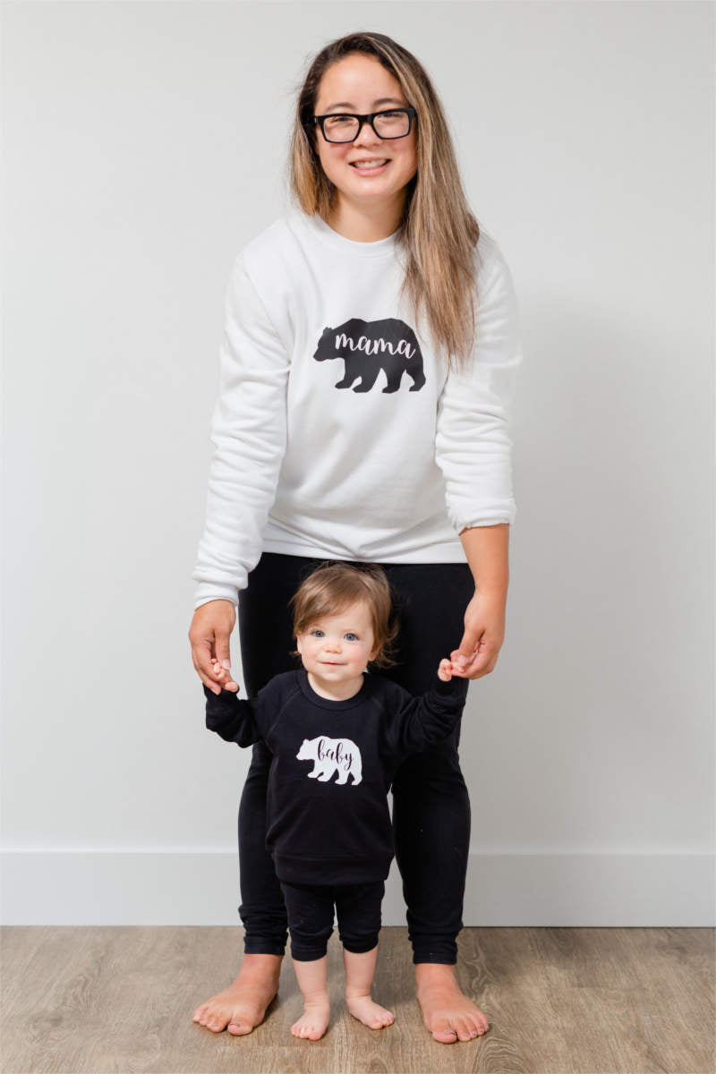 "A mother is standing behind her baby, holding her hands.  The mom is wearing a white sweatshirt that says ""mama"" inside a bear.  The baby is wearing a black sweatshirt that says ""baby"" inside a bear."