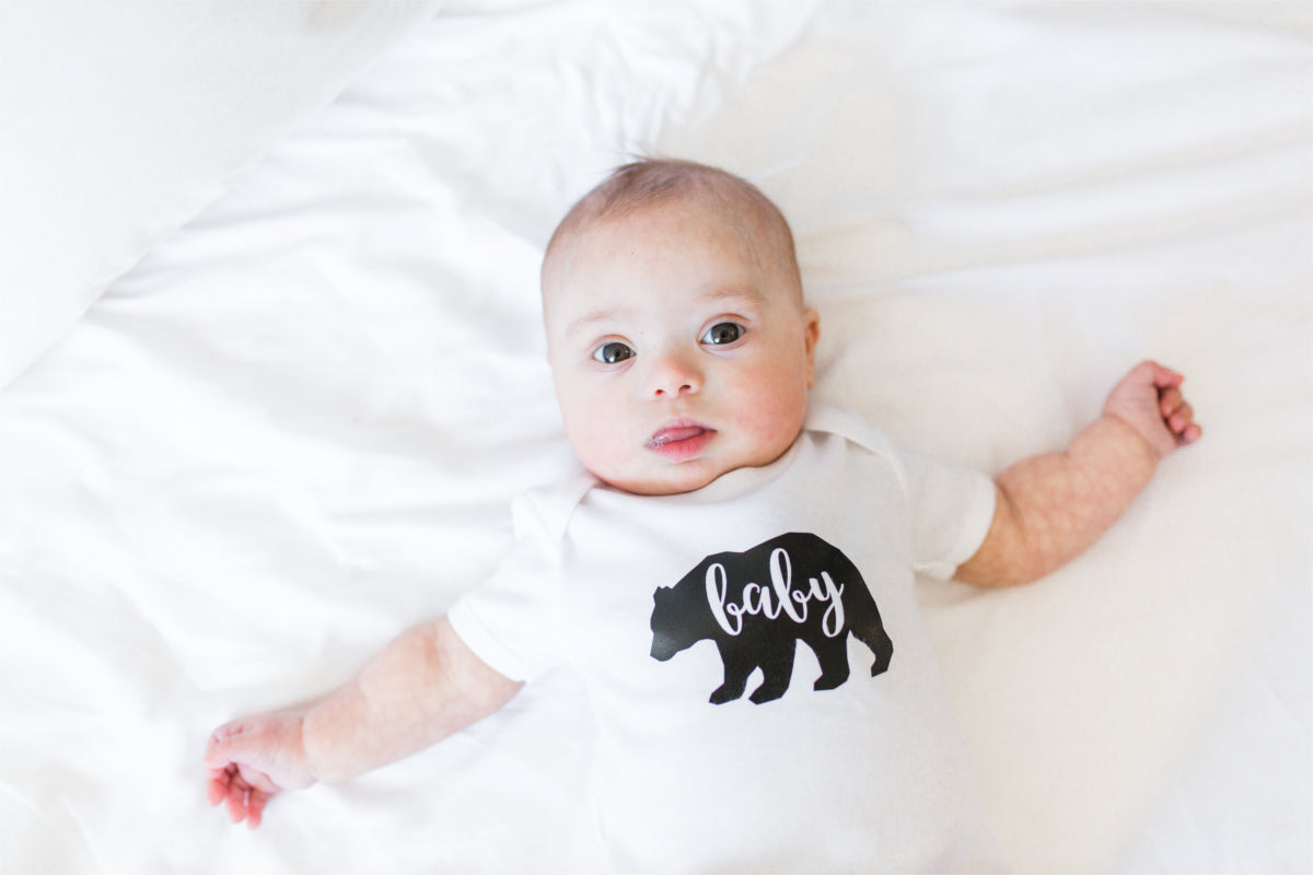 "Baby sprawled across a bed wearing a ""baby bear"" bodysuit."