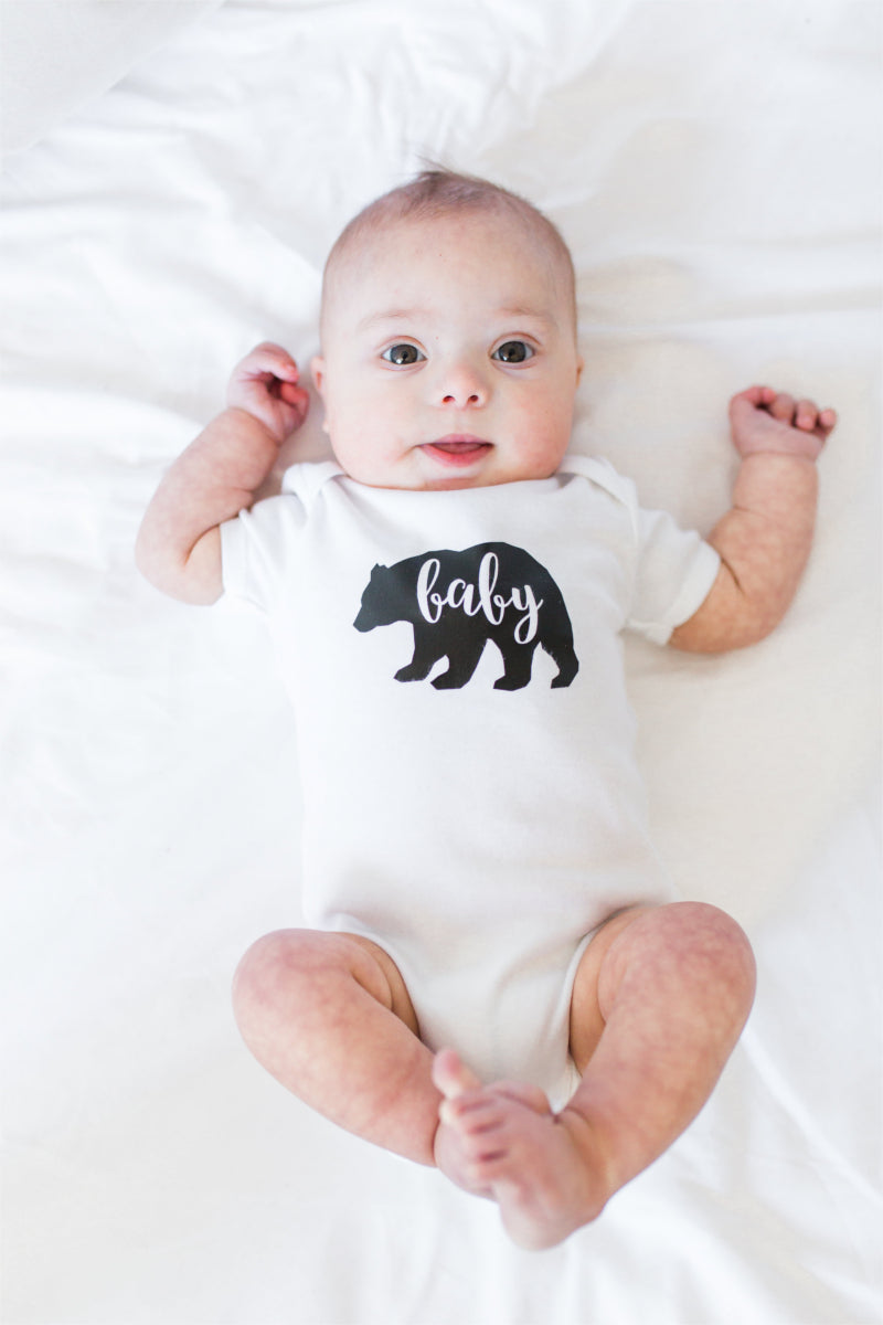 "Baby boy lying on a bed and smiling at the camera.  He is wearing a ""baby bear"" white bodysuit."