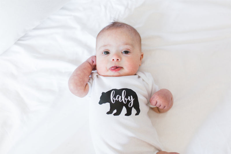Baby boy curled up on a bed wearing a baby bear bodysuit.