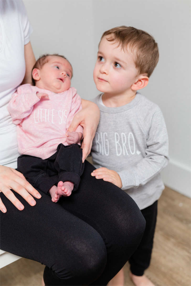 "A little boy is standing beside someone holding a baby girl.  The baby's pink sweater says ""little sis"" and the boy's grey sweater says ""big bro""."