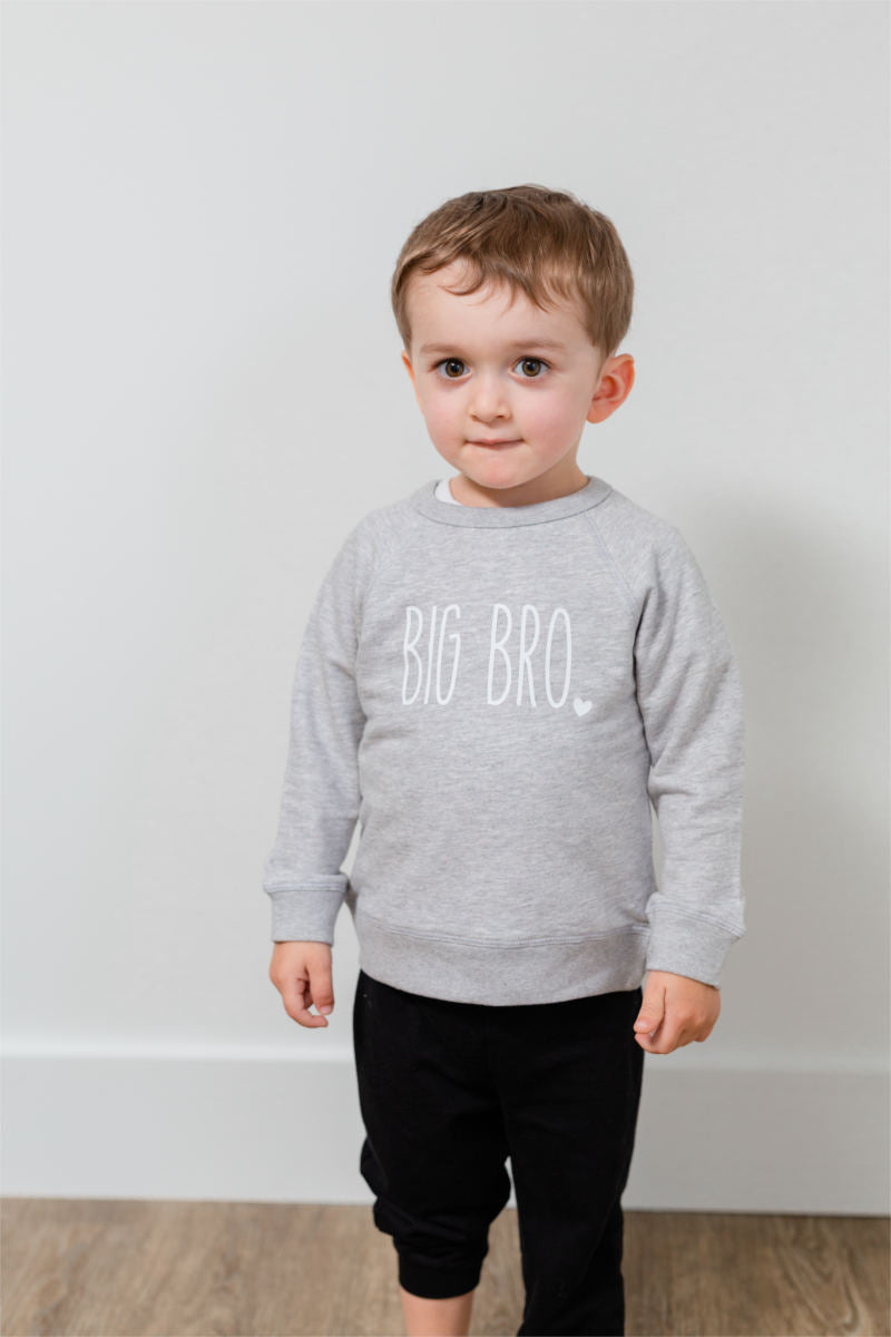 "A boy stands in front of a white wall, wearing a grey sweatshirt and black pants. His sweatshirt says ""big bro""."