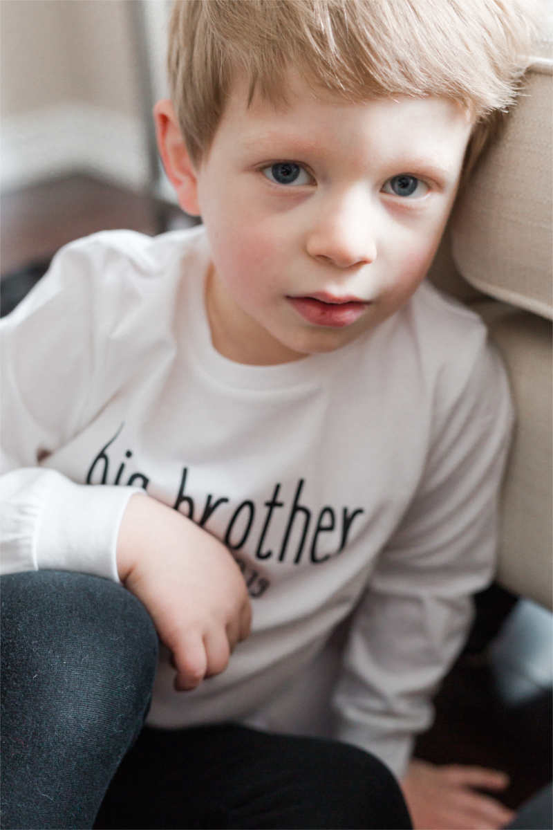 "A boy is sitting on the floor looking into the camera.  He is wearing jeans and a white long-sleeve shirt that says ""big brother."""