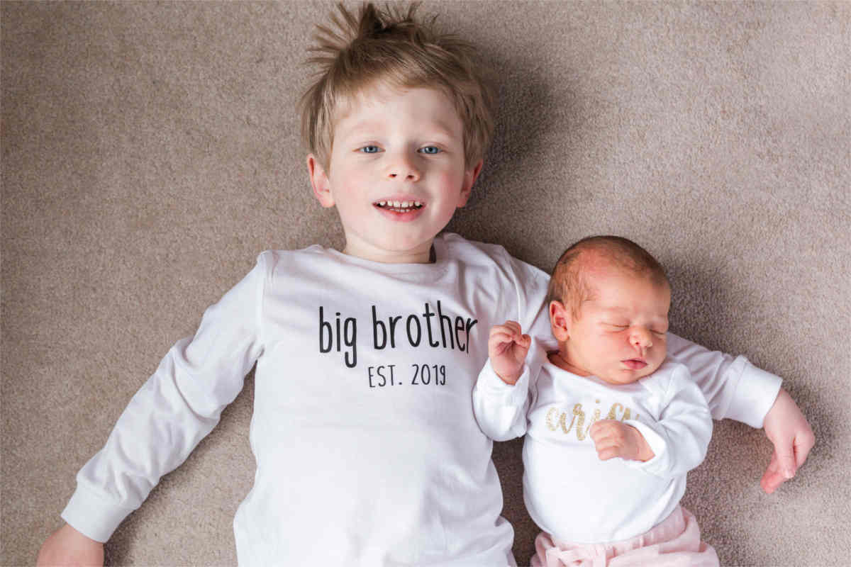 "A boy and a baby girl are cuddled together on the floor.  His white shirt says, ""big brother est. 2019."""