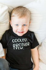 "A boy is resting on a pillow, wearing a black tee that says ""coolest brother ever."""