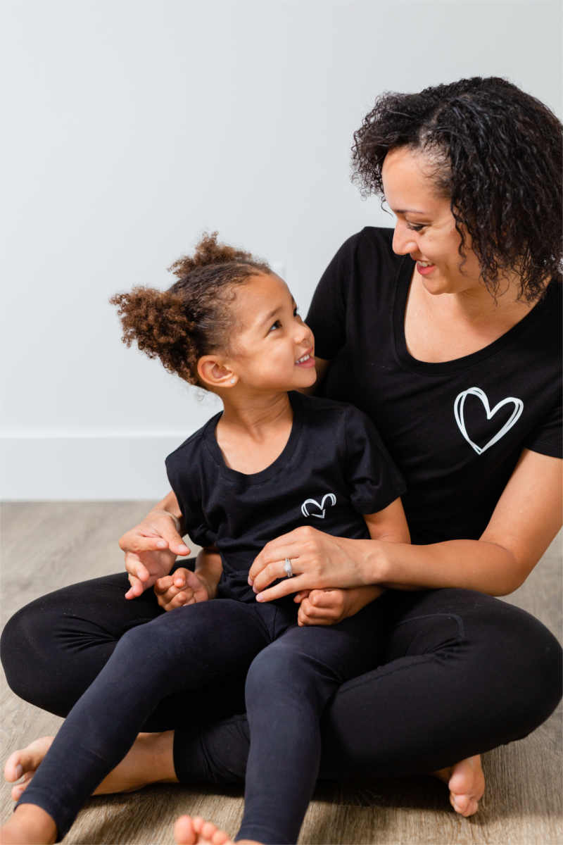 A mother is sitting cross-legged with her daughter on her lap.  They both have dark, curly hair and are smiling at each other.  Their black t-shirts have a white heart on the left chest.