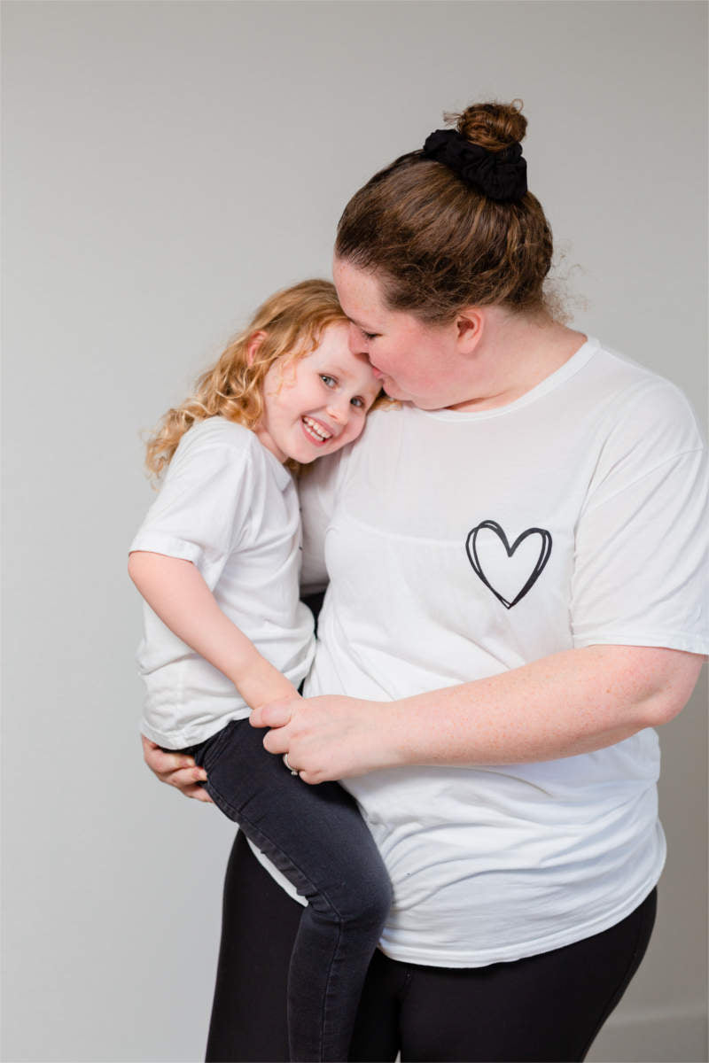 A mother is holding her daughter and kissing her on the forehead.  They are wearing matching white t-shirts with a black heart on the left chest.