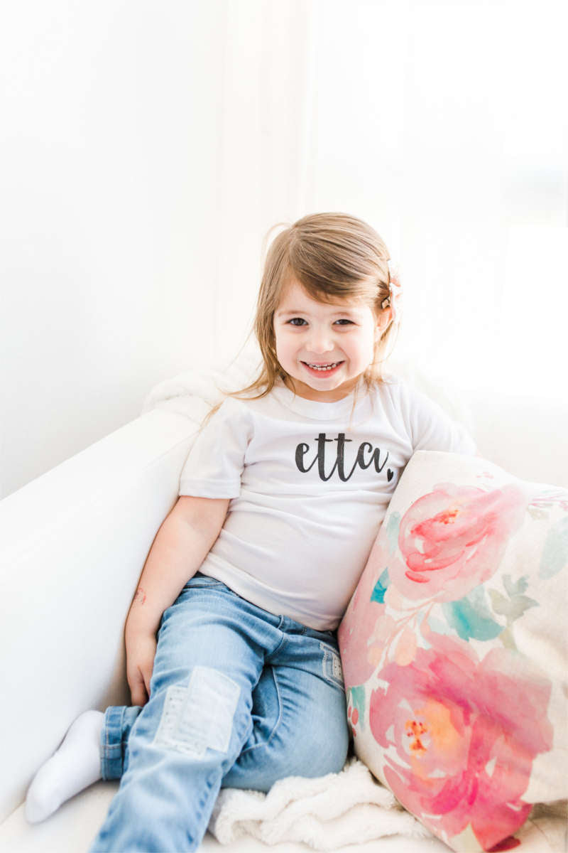"A girl is sitting on a chair with a floral pillow.  Her tee says ""Etta."""