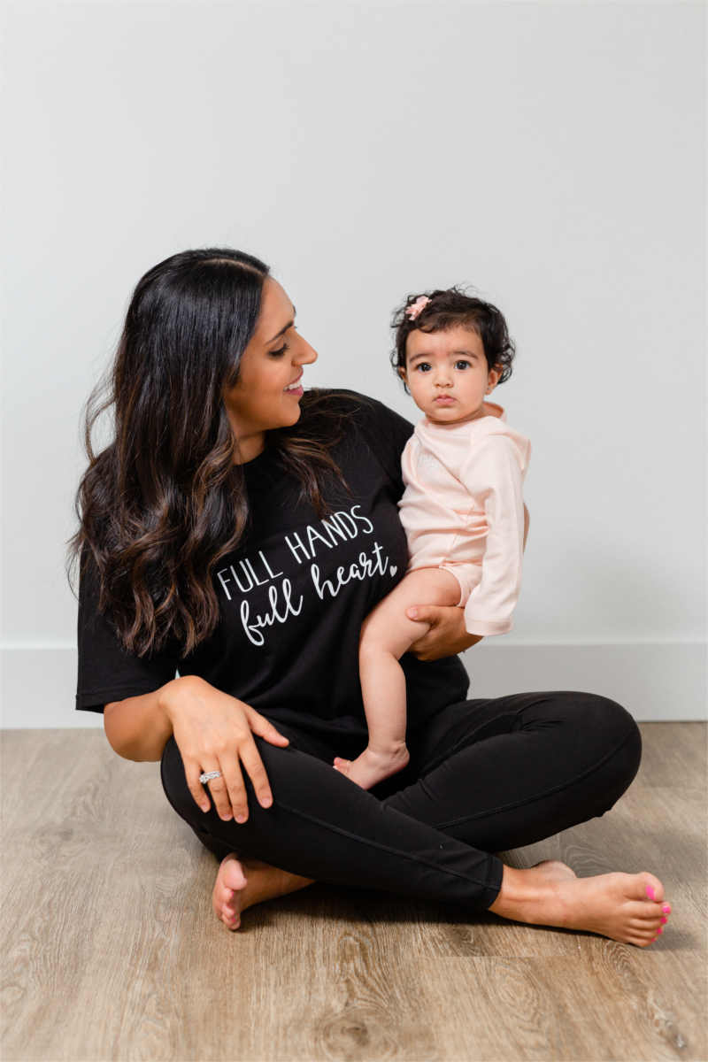 "A mother is sitting cross-legged with her daughter on her lap.  They both have dark, wavy hair.  The mom is wearing a black shirt that says ""full hands, full heart."""