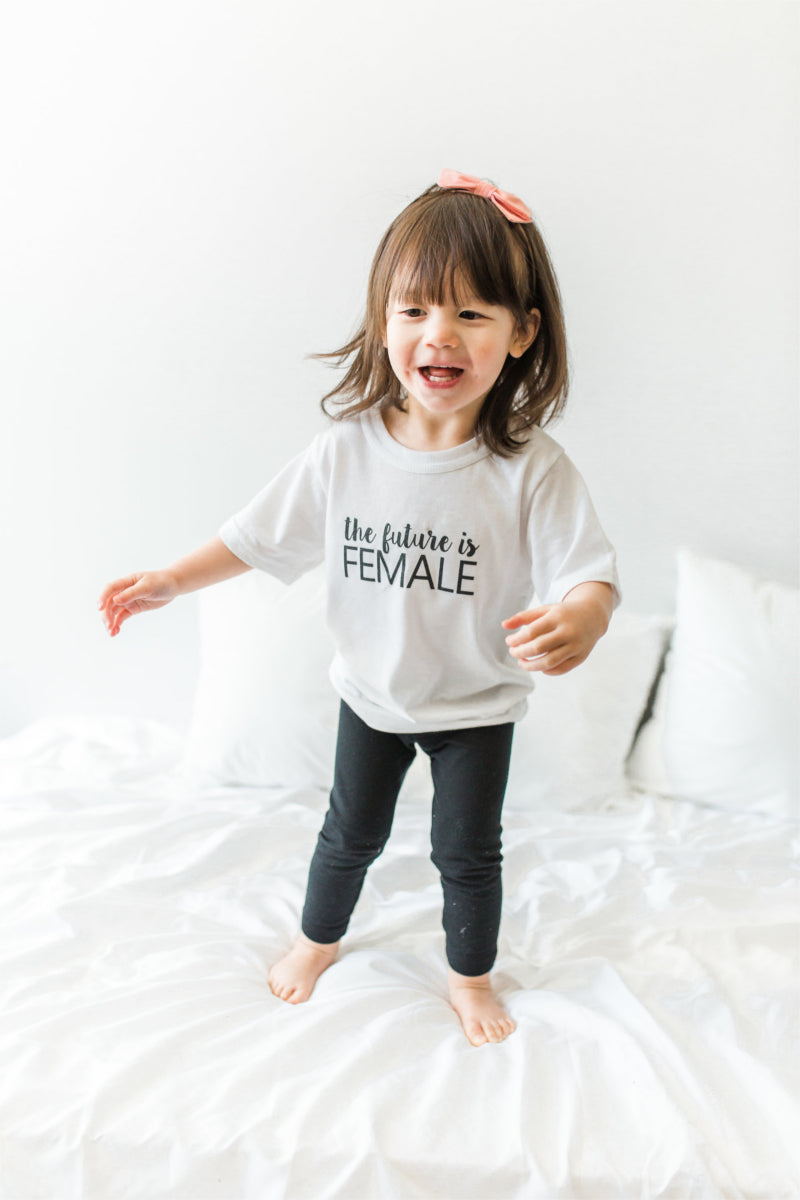 "A girl is jumping on a bed.  She is wearing a white shirt that says ""the future is female."""