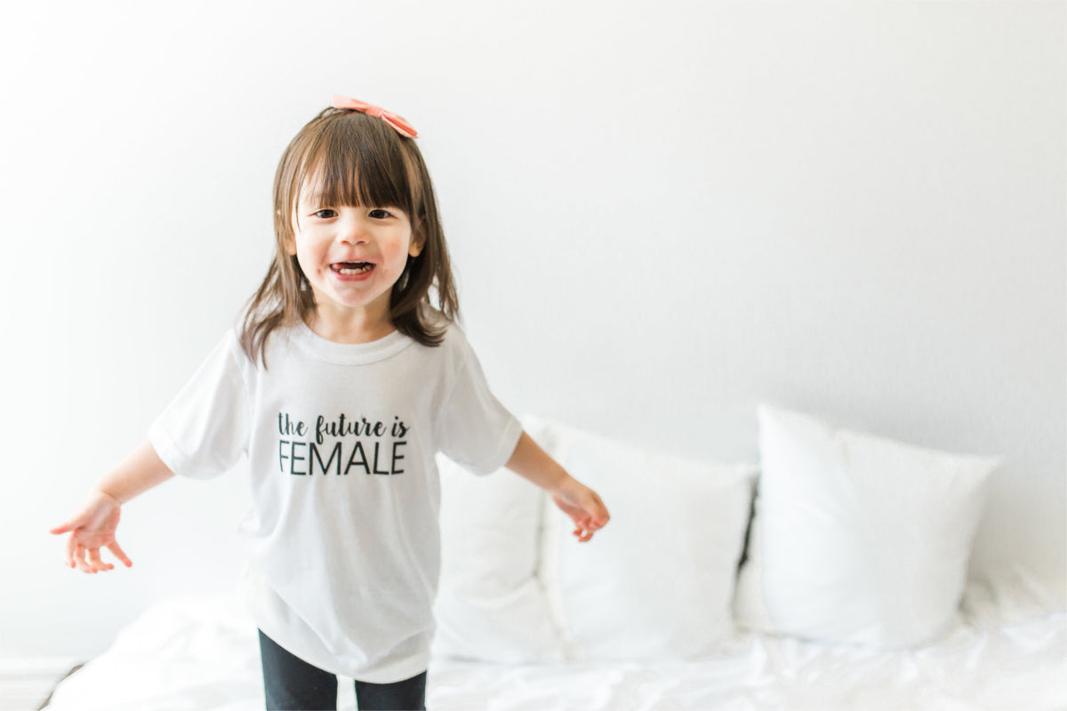 "A girl is standing on a bed, smiling with her arms out to the side.  She is wearing a shirt that says, ""the future is female."""