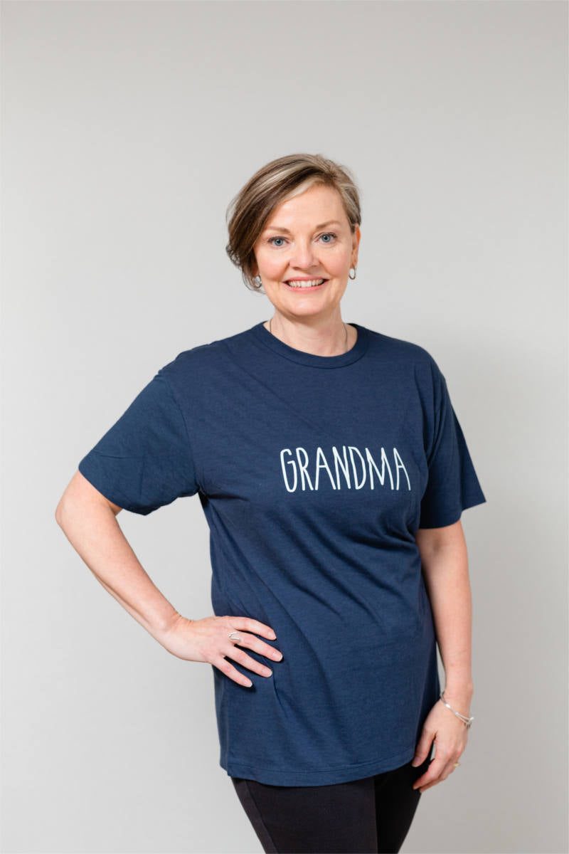 "A woman is standing with her hand on her hip, smiling at the camera. She is wearing a navy t-shirt that says ""GRANDMA""."