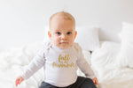 "A baby is sitting on a bed.  She is wearing a bodysuit that says ""fall is my favourite""."