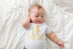 "A baby is lying on a bed.  He is wearing a bodysuit with a pineapple on it that says ""so fresh."""
