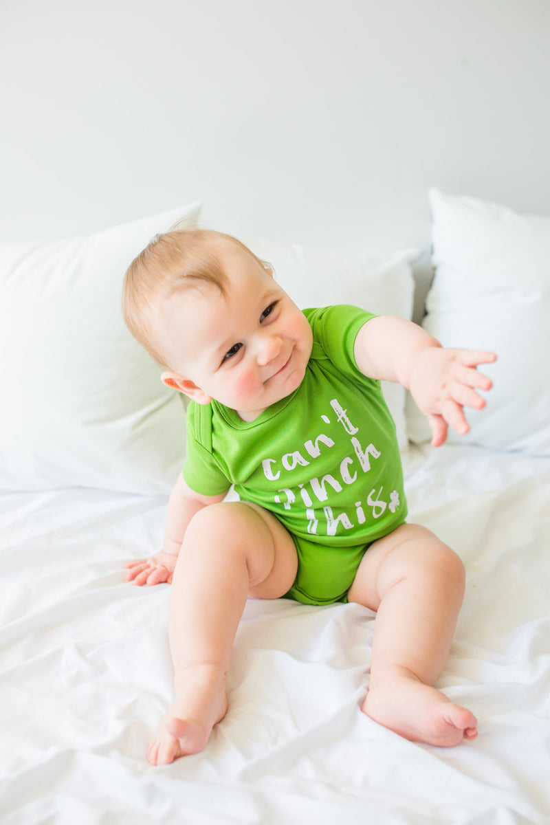 "A baby is sitting on a bed.  He is wearing a green bodysuit that says, ""can't pinch this""."