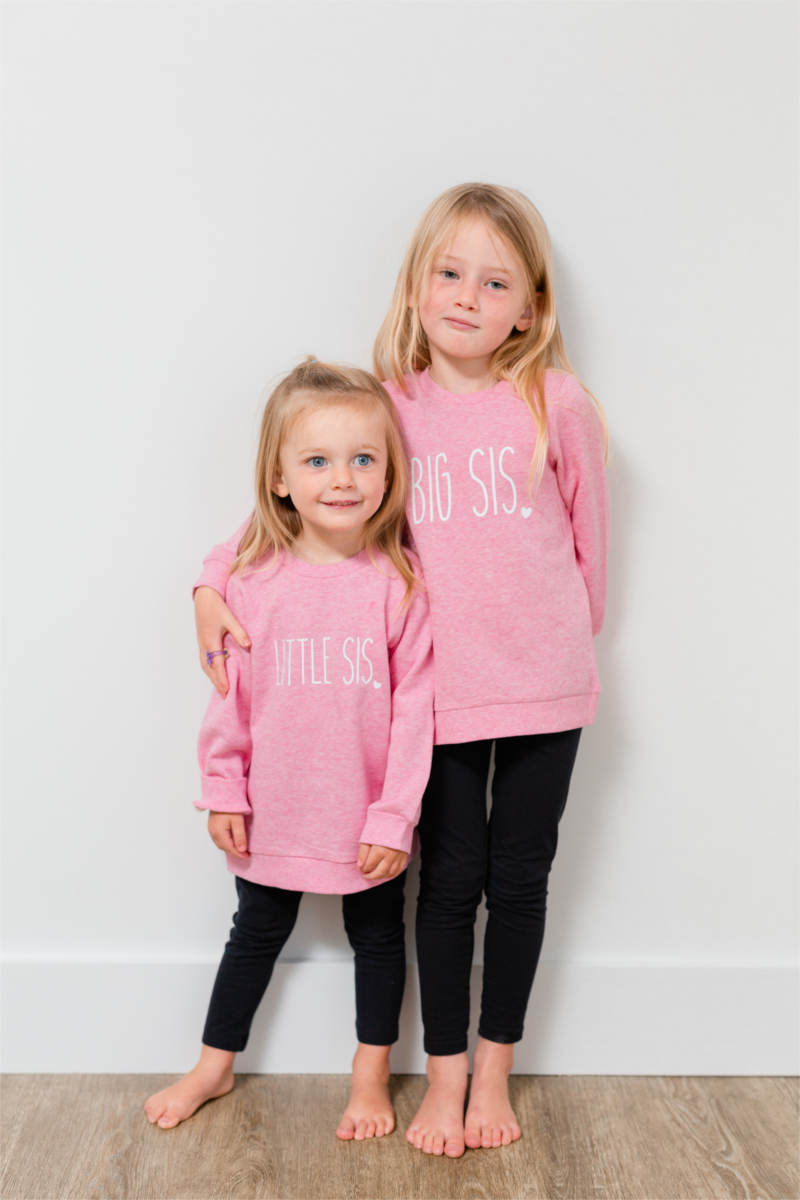 "Two sisters are standing against a wall wearing pink sweaters.  Their shirts say ""big sis"" and ""little sis"".  The older sister has her arm around the younger sister."