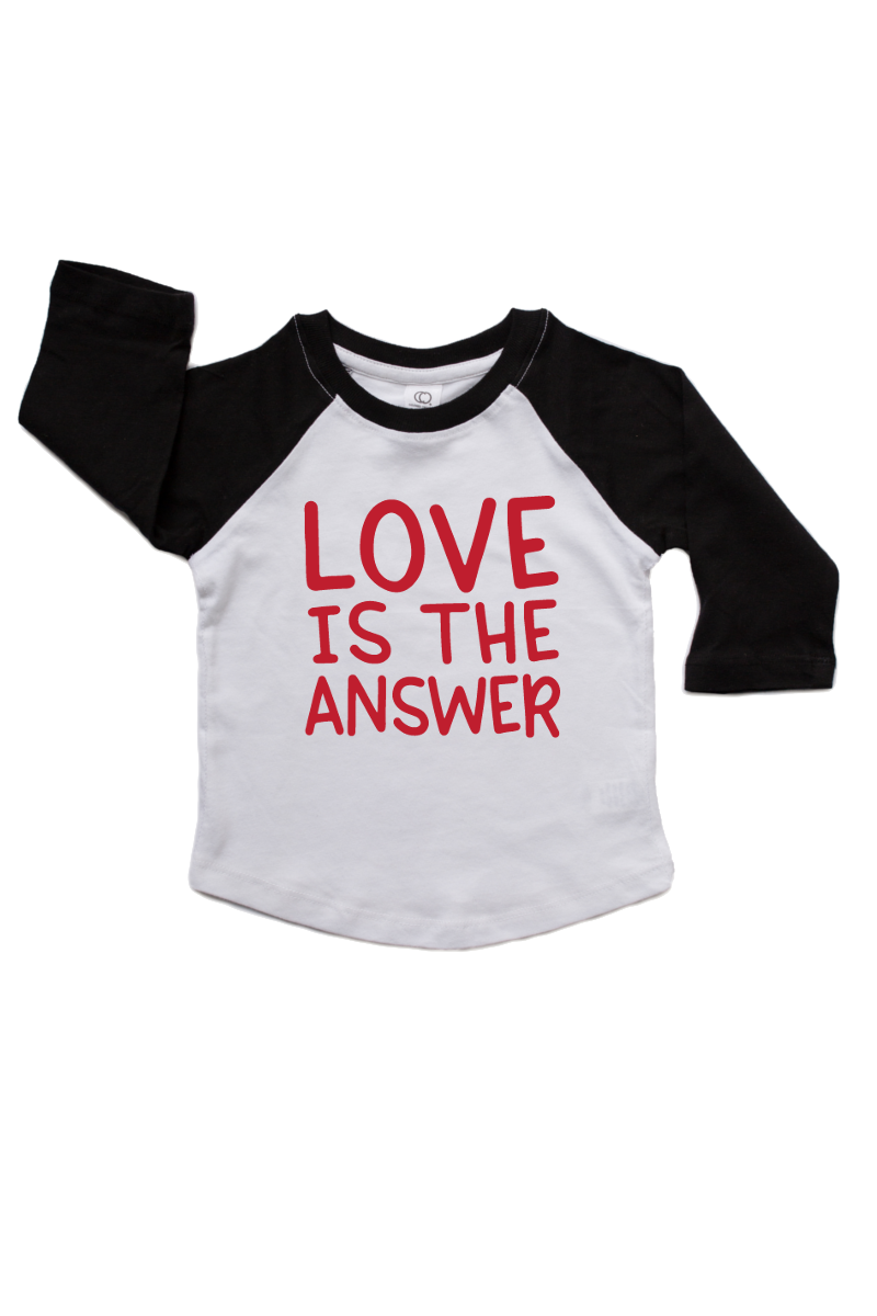 "A black and white baseball shirt that says ""love is the answer""."