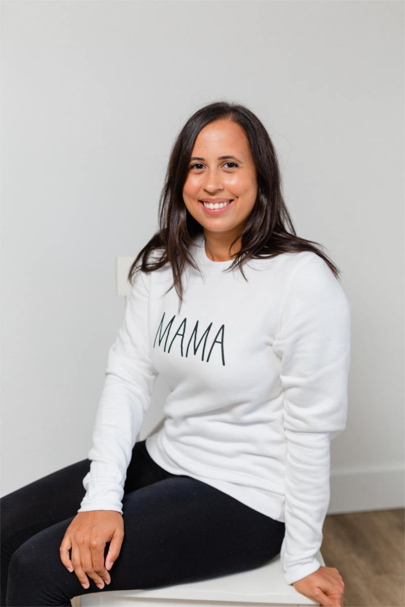"A woman is sitting on a chair, smiling at the camera.  She has long black hair, black pants, and a white sweatshirt that says ""MAMA."""