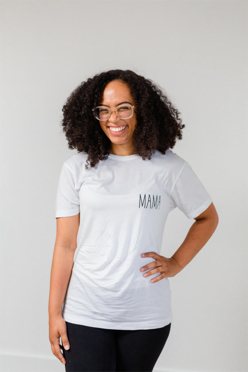"A woman is smiling at the camera with her hand on her hip.  She has glasses and black curly hair. She is wearing black pants and a white t-shirt.  Her shirt says ""mama."""