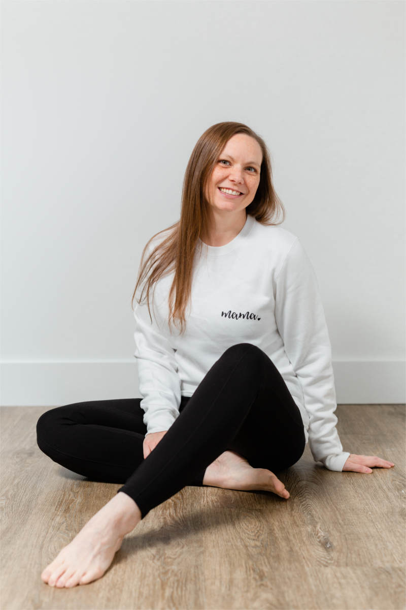 "A woman is sitting on the floor, wearing black leggings and a white sweatshirt.  She has long brown hair and is smiling.  Her sweater says ""mama""."