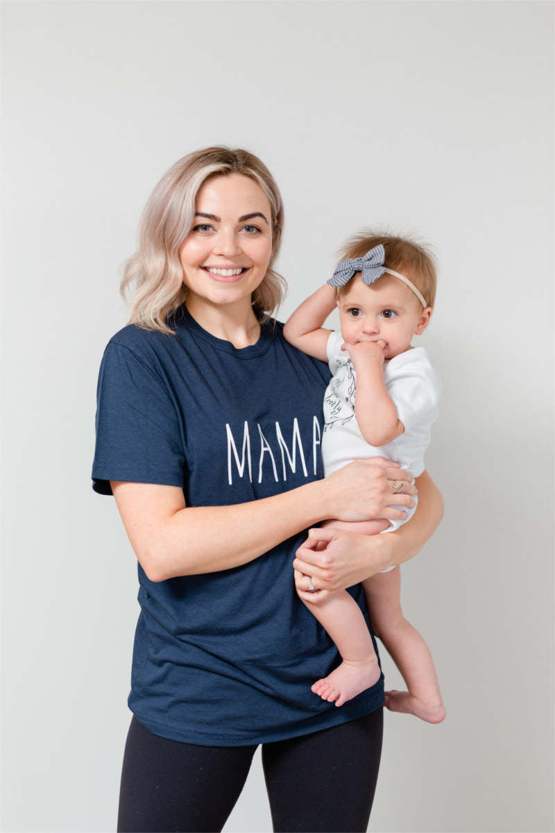 "A mother is holding her baby girl.  Her daughter has a bow in her hair.  The mom is wearing a blue t-shirt that says ""mama."""