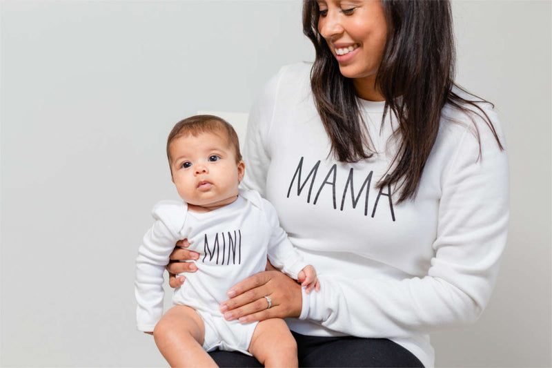 "A mother is sitting with her baby on her knee.  The baby's white bodysuit says ""mini"" and her white sweatshirt says ""mama."""