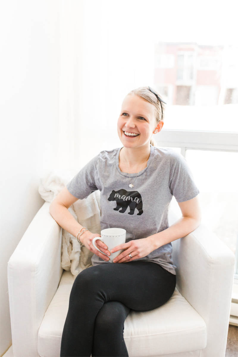 "Woman holding a coffee cup, smiling and sitting on a chair near a window.  She is wearing a grey t-shirt that has a bear on it.  The word ""mama"" is inscribed inside the bear."