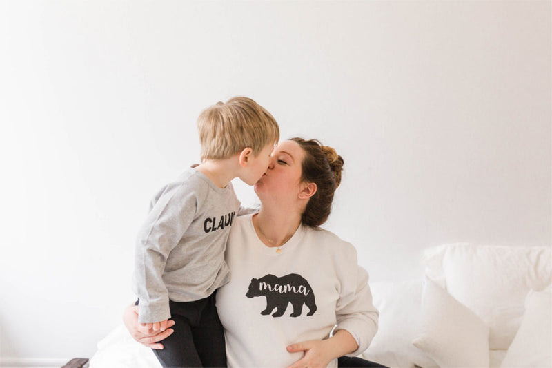 Woman and son kissing.  Woman is wearing a mama bear sweatshirt and holding her pregnant belly.