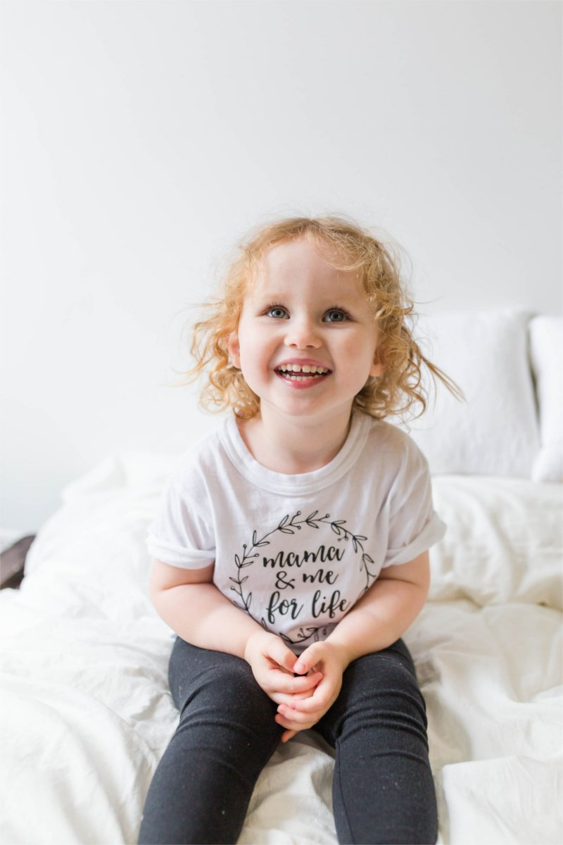 "A young girl is sitting on a bed, smiling up at the camera.  Her shirt says ""mama and me for life""."