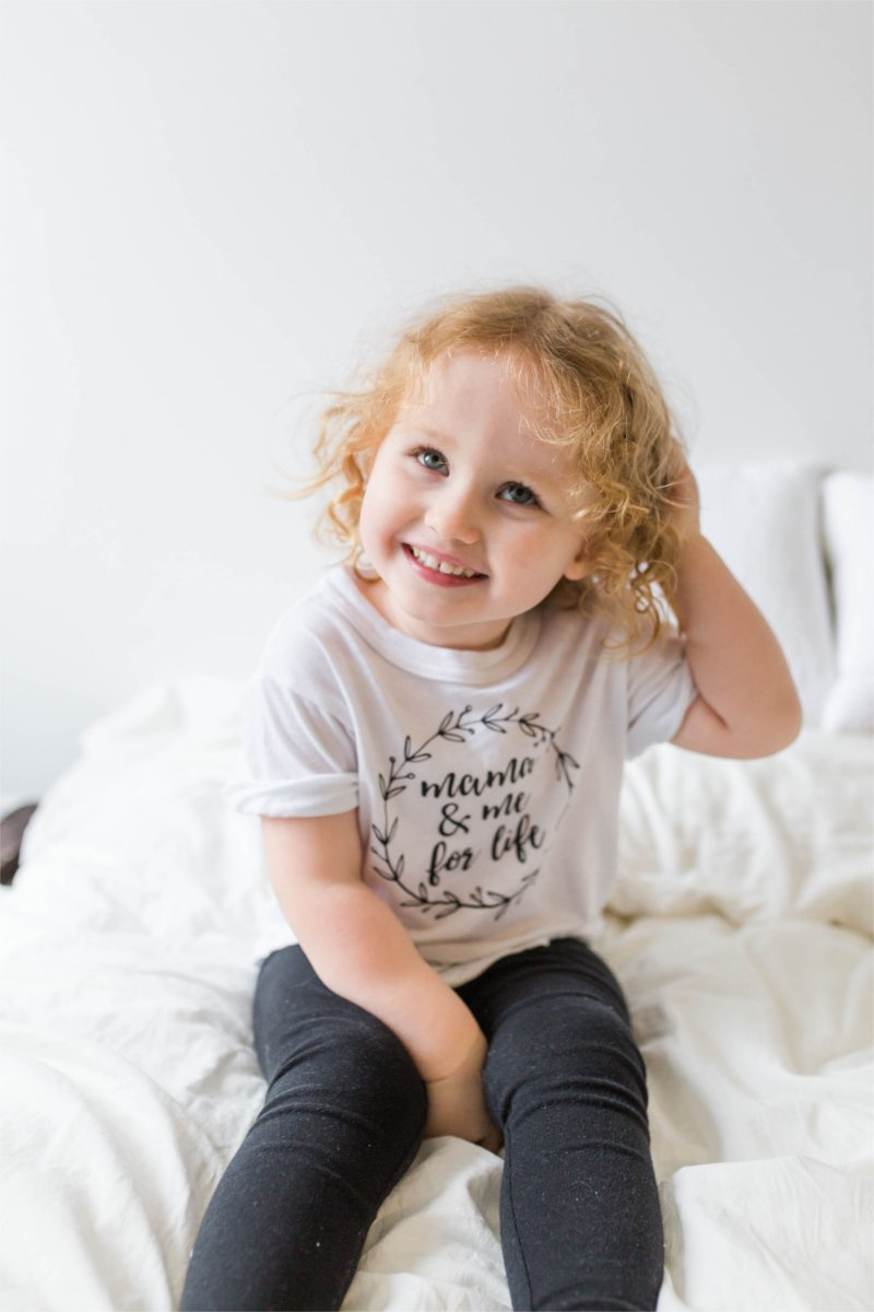 "A young girl is sitting on a bed, smiling at someone off camera.  Her shirt says ""mama and me for life""."