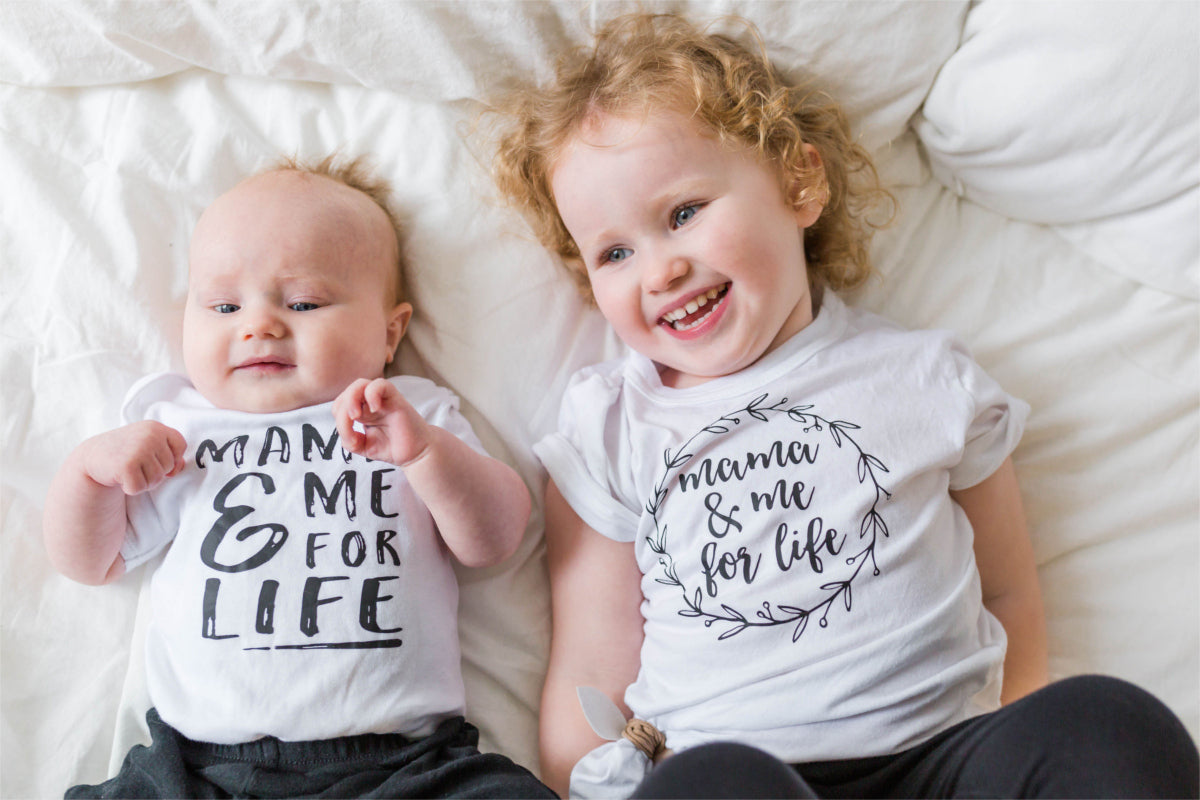 "A baby boy and little girl are lying side by side on a bed.  They are smiling at someone off camera.  Their shirts say, ""mama and me for life."""