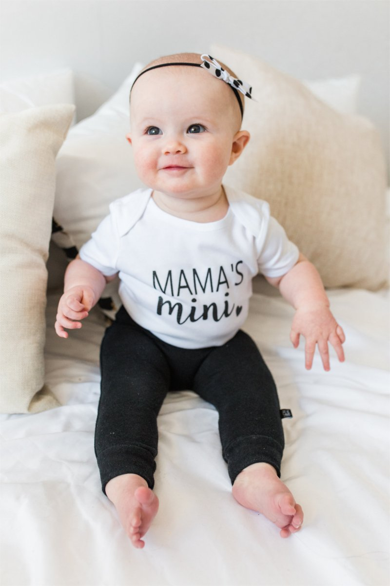 "A baby girl is sitting on a bed smiling up at the camera.  She is wearing black leggings and a white bodysuit that says ""mama's mini."""