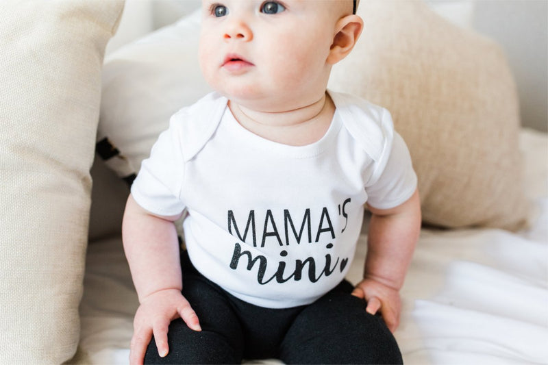 "A baby girl is sitting on a bed staring into the distance.  She is wearing black leggings and a white bodysuit that says ""mama's mini."""