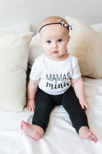 "A baby girl is sitting on a bed staring at the camera.  She is wearing black leggings and a white bodysuit that says ""mama's mini."""