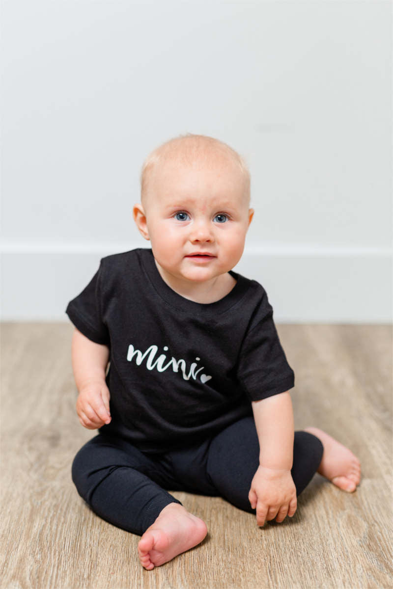 "A baby girl is sitting on the floor.  She has on a black t-shirt and pants.  Her shirt says ""mini""."
