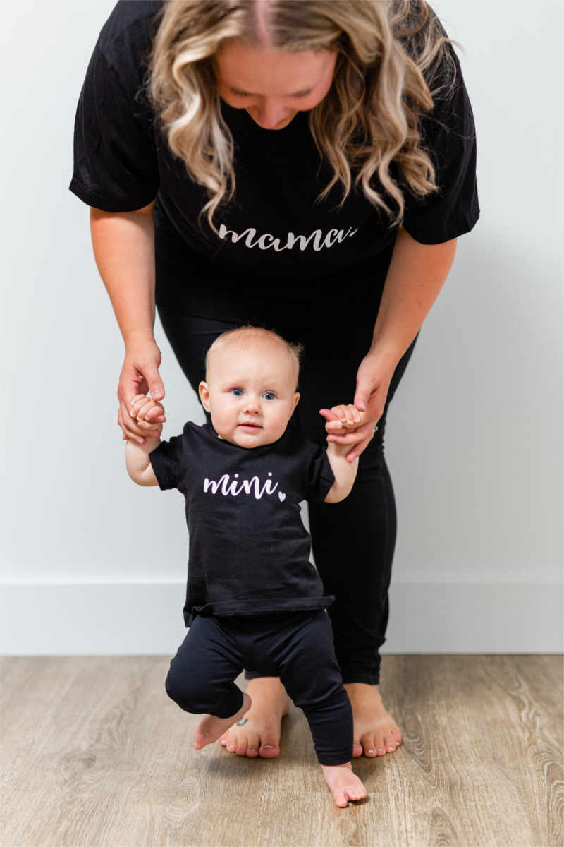 "A woman is holding up a baby girl.  They are both wearing a black t-shirt and leggings.  Their shirts say ""mama"" and ""mini""."