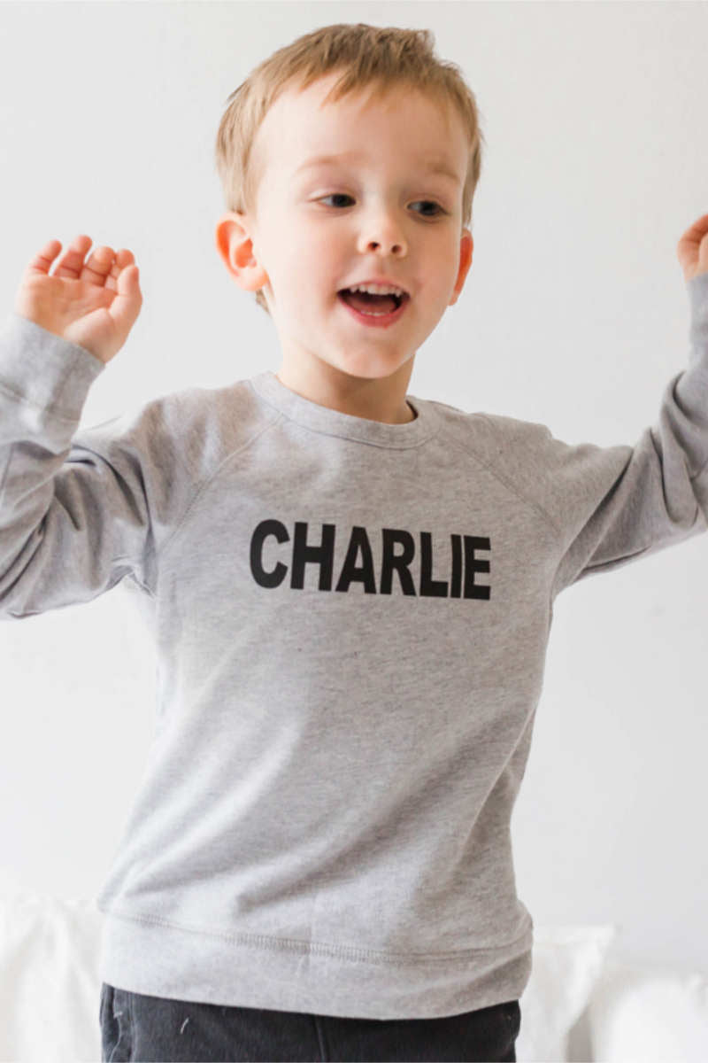 "A boy is wearing a grey sweatshirt that says ""Charlie"" across the chest."