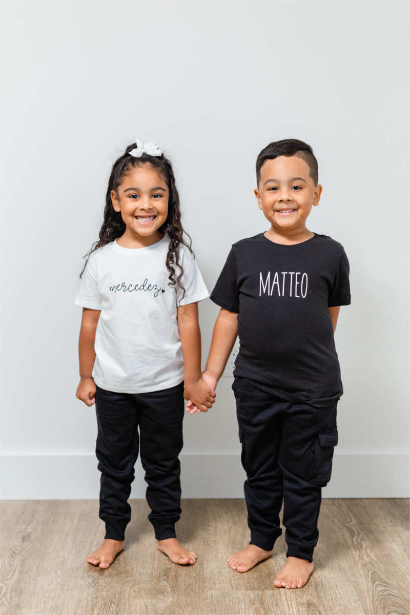 "A brother and sister are standing holding hands.  She has long black hair and a white bow.  Her white t-shirt says ""mercedez"".  He has short black hair and a black t-shirt that says ""MATTEO""."
