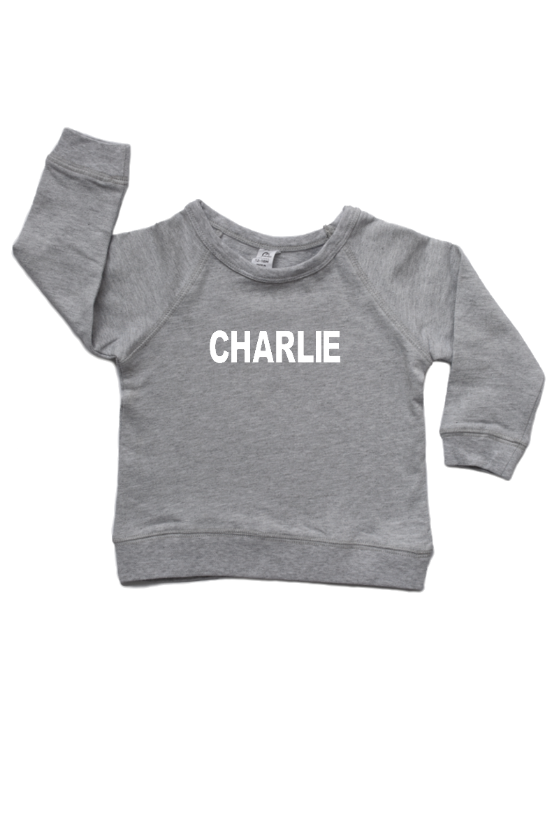 "Grey sweatshirt with the name ""Charlie"" written on it."