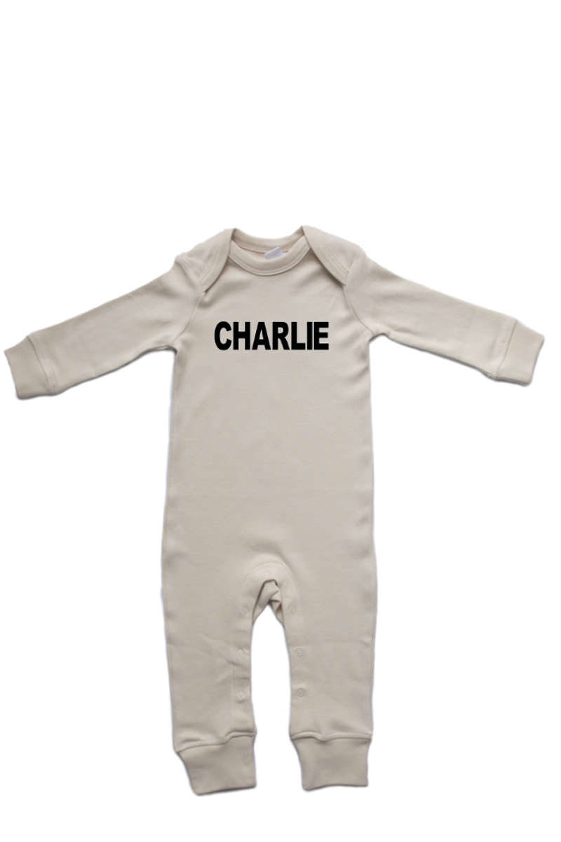 "A natural white baby romper with ""Charlie"" written on it."